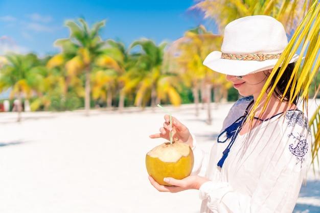 Trinkende kokosmilch der jungen frau am heißen tag auf dem strand. Premium Fotos