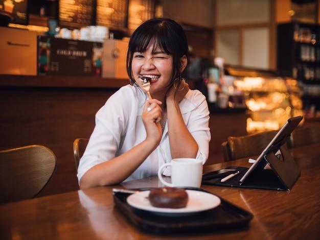 Trinkender kaffee der asiatin im café und anwendung der laptop-computers für arbeitsgeschäft Premium Fotos