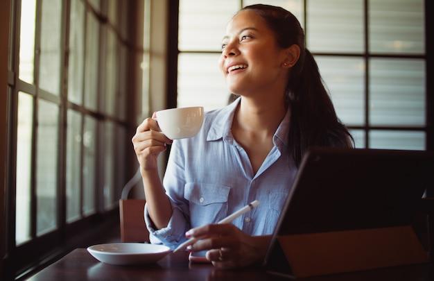 Trinkender kaffee der asiatin und arbeiten mit laptop-computer im café Premium Fotos