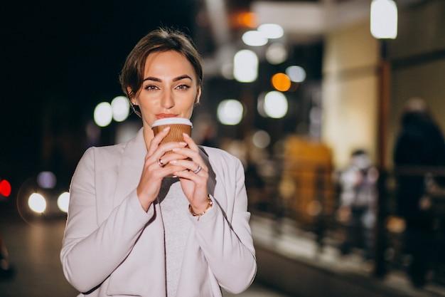 Trinkender kaffee der frau draußen in der straße nachts Kostenlose Fotos