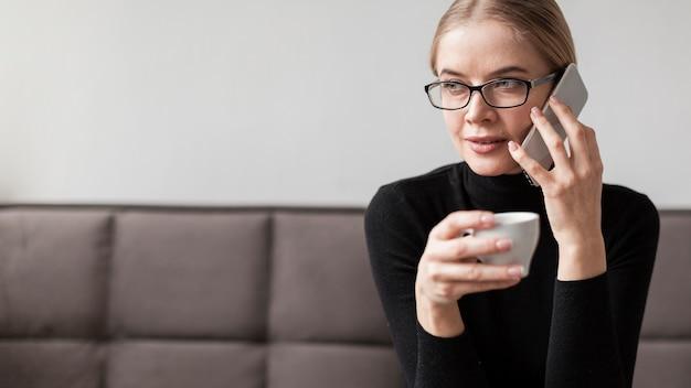 Trinkender kaffee der frau und unterhaltung über telefon Kostenlose Fotos