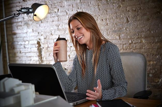 Trinkender kaffee der geschäftsfrau, der im büro arbeitet Premium Fotos