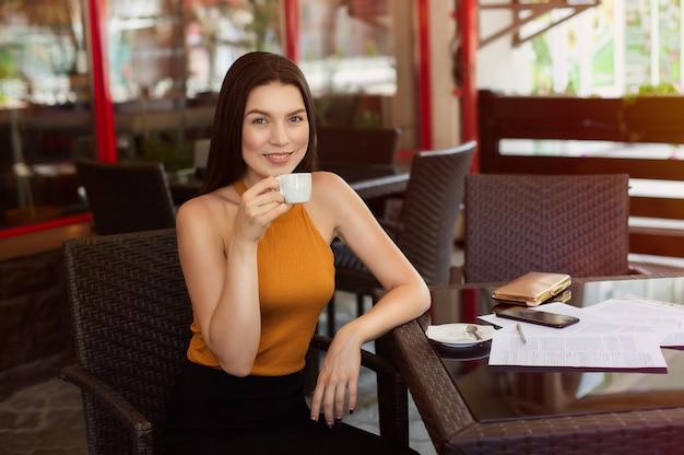 Trinkender kaffee der glücklichen geschäftsfrau mit zerstreuten papieren auf dem tisch. gute nachrichten, freude und glück. Premium Fotos