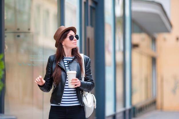 Trinkender kaffee der glücklichen jungen städtischen frau in der europäischen stadt. touristische frau der reise mit heißem getränk draußen während der feiertage in europa. Premium Fotos