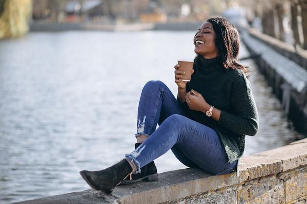 Trinkender kaffee der jungen afroamerikanerfrau am see Kostenlose Fotos