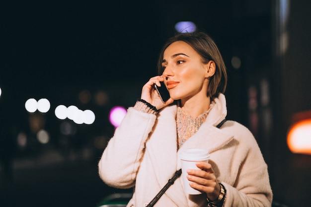 Trinkender kaffee der jungen frau an der nachtstraße Kostenlose Fotos