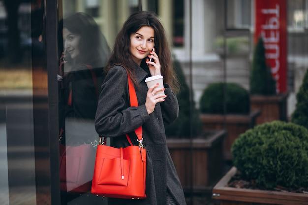 Trinkender kaffee der jungen frau und anwendung des telefons in der stadt Kostenlose Fotos