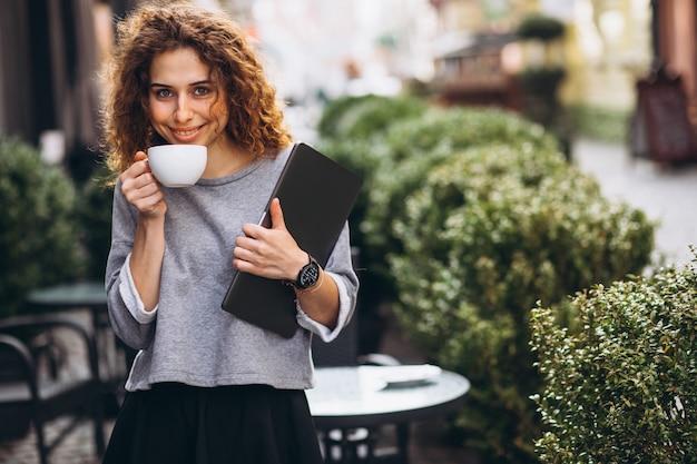Trinkender kaffee der jungen geschäftsfrau außerhalb des cafés, das laptop hält Kostenlose Fotos