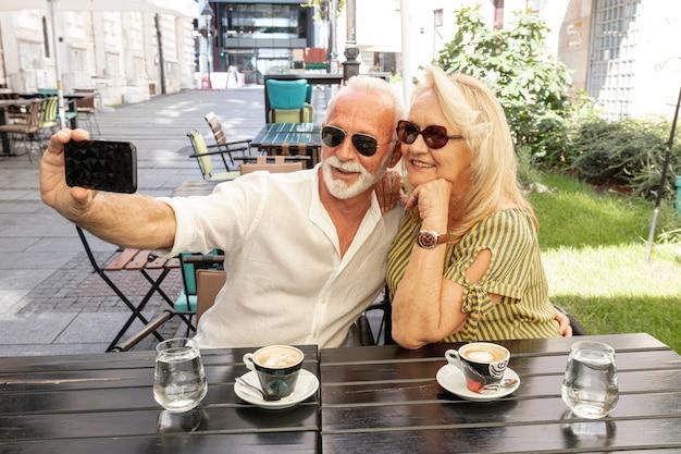 Trinkender kaffee der paare und nehmen eines selfie Kostenlose Fotos