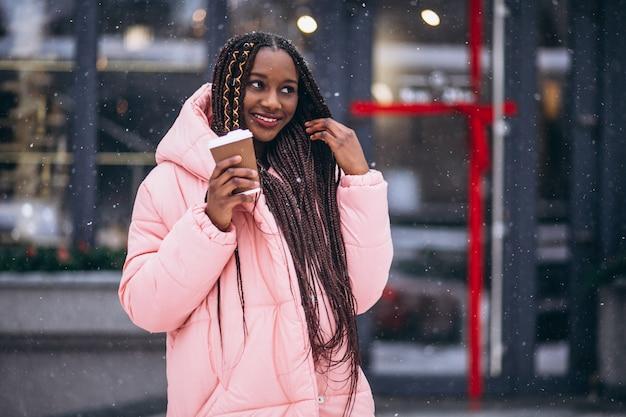 Trinkender kaffee des afroamerikaners an einem wintertag Kostenlose Fotos