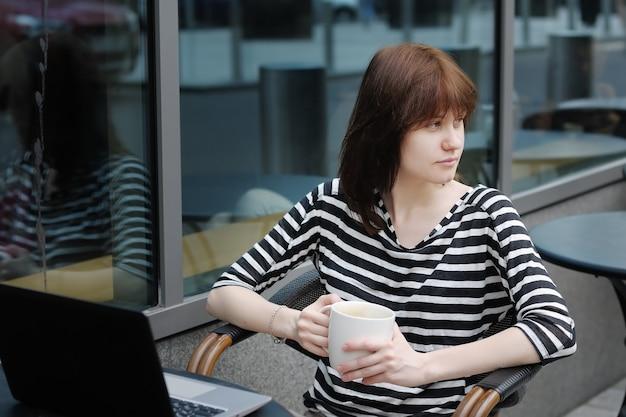 Trinkender kaffee des durchdachten mädchens und anwendung des laptops in einem café im freien Premium Fotos