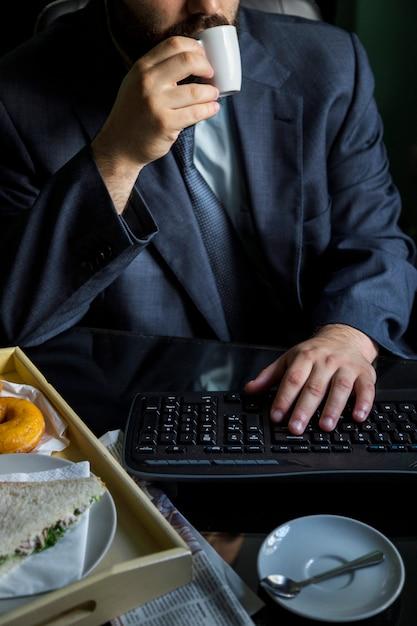 Trinkender kaffee des geschäftsmannes mit tastatur auf schreibtisch Kostenlose Fotos