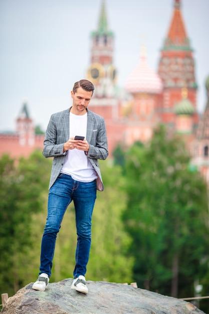 Trinkender kaffee des glücklichen jungen städtischen mannes in der europäischen stadt. Premium Fotos