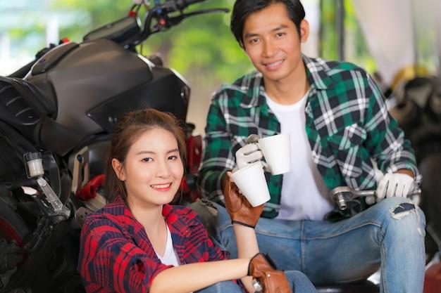 Trinkender kaffee des glücklichen paars an einer motorradreparaturwerkstatt Premium Fotos