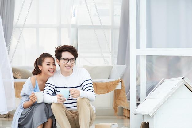 Trinkender kaffee des glücklichen paars Kostenlose Fotos