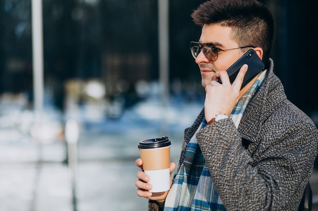 Trinkender kaffee des jungen gutaussehenden mannes draußen und mit telefon Kostenlose Fotos
