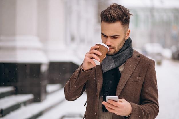 Trinkender kaffee des jungen gutaussehenden mannes und unterhaltung am telefon Kostenlose Fotos