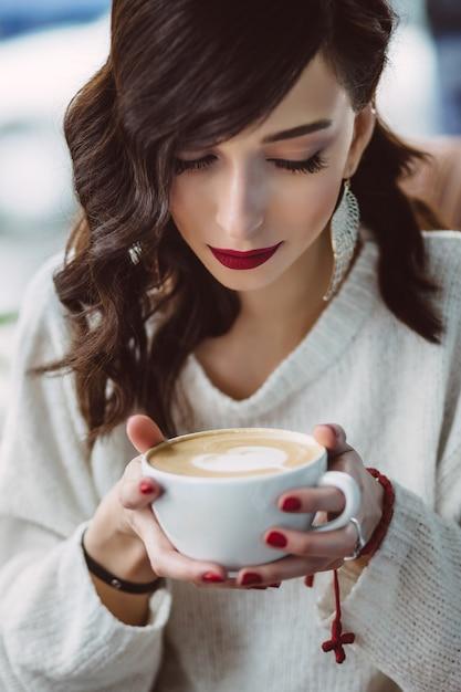 Trinkender kaffee des jungen mädchens in einem modischen café Kostenlose Fotos
