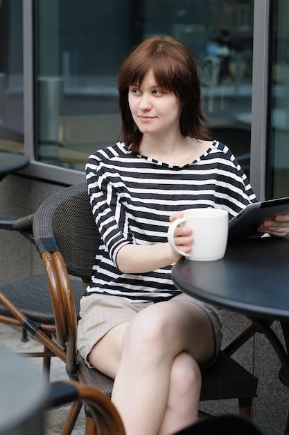 Trinkender kaffee des mädchens und anwendung des tablet-computers in einem café im freien Premium Fotos