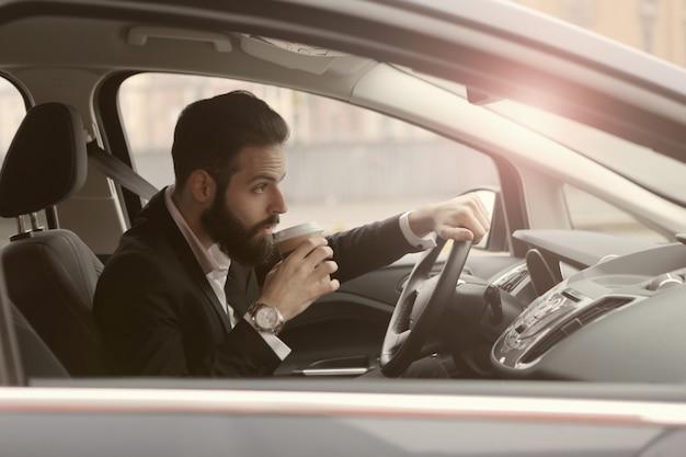 Trinkender kaffee des mannes in einem auto Premium Fotos