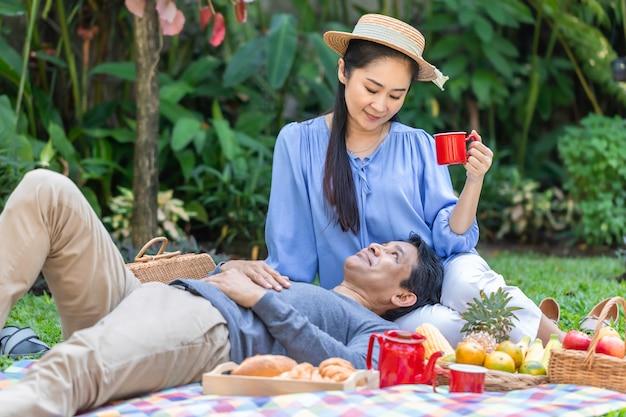 Trinkender kaffee und picknick der älteren asiatischen paare am garten. Premium Fotos