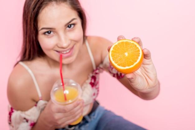 Trinkender saft der frau und holding geschnittene orange Kostenlose Fotos