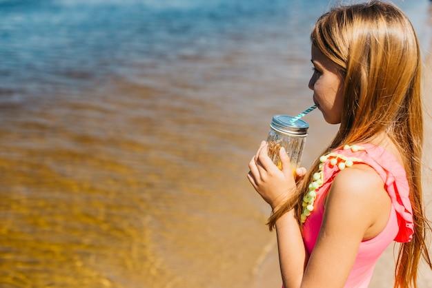 Trinkender saft des kleinen mädchens bei der stellung auf strand Kostenlose Fotos