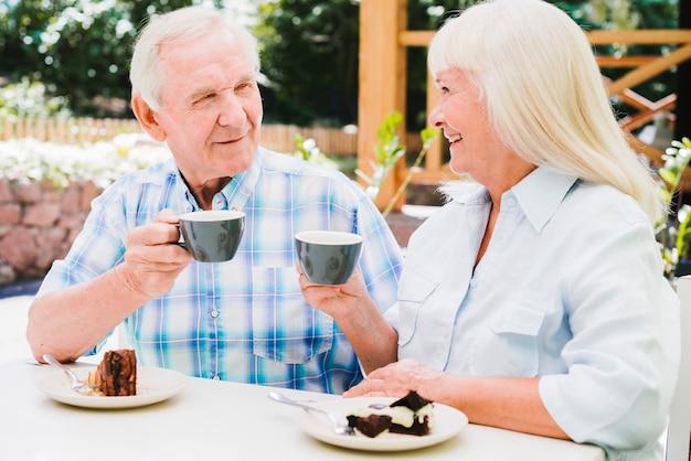 Trinkender tee der älteren paare auf freienveranda Kostenlose Fotos