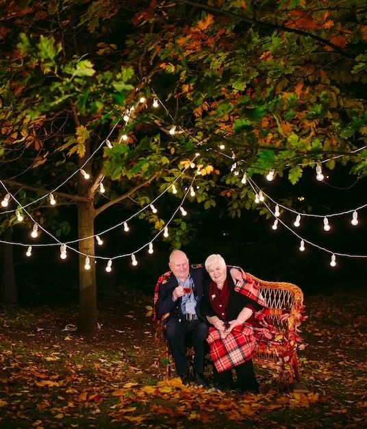 Trinkender tee der glücklichen älteren paare am abend, der auf der couch sitzt. Premium Fotos