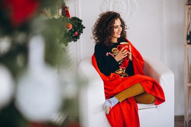 Trinkender tee der jungen frau durch weihnachtsbaum Kostenlose Fotos
