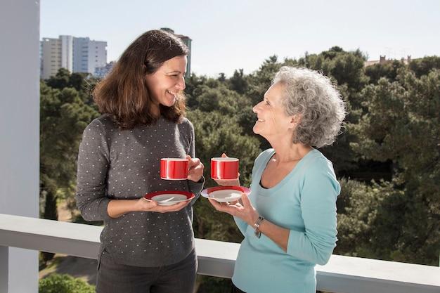 Trinkender tee der mittleren erwachsenen frau mit ihrer älteren mutter auf balkon Kostenlose Fotos