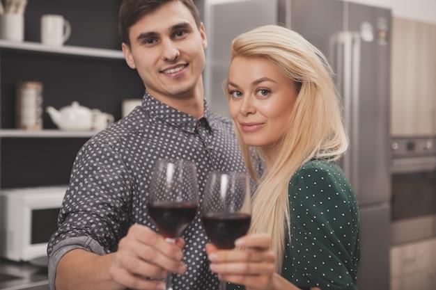 Trinkender wein des glücklichen paars zusammen zu hause Premium Fotos