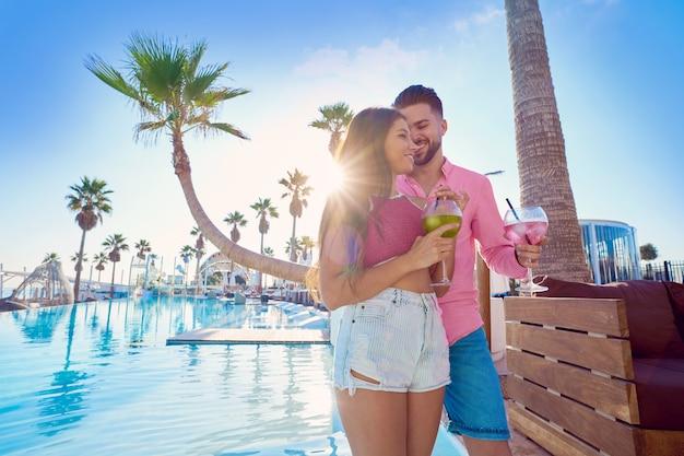Trinkendes cocktail der jungen paare im poolurlaubsort Premium Fotos