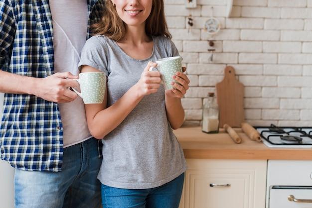 Trinkendes gebräu der glücklichen umfassungspaare und stellung in der küche Kostenlose Fotos