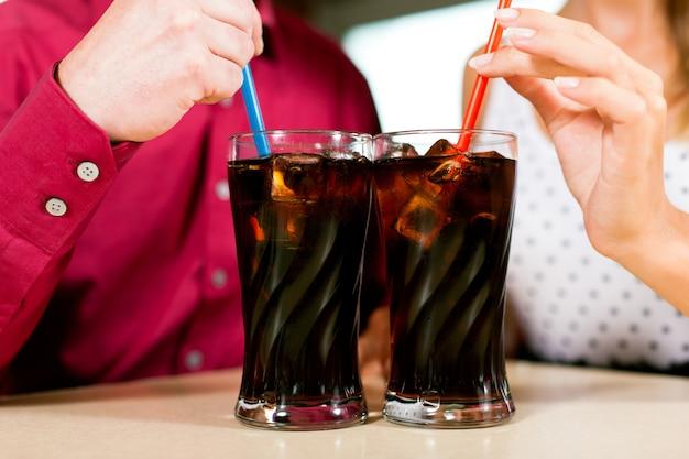 Trinkendes soda der paare in einer bar Premium Fotos