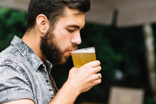 Trinkglas des gutaussehenden mannes bier an draußen Premium Fotos