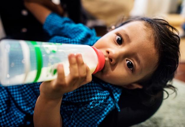 Trinkmilch des jungen indischen jungen von der flasche Premium Fotos