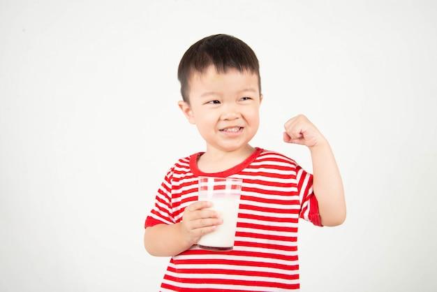 Trinkmilch des kleinen asiatischen jungen vom glas mit glücklichem gesicht Premium Fotos