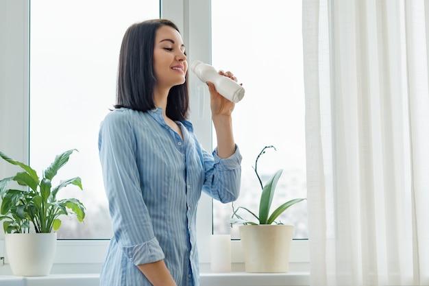 Trinkmilchgetränkjoghurt der frau von der flasche Premium Fotos