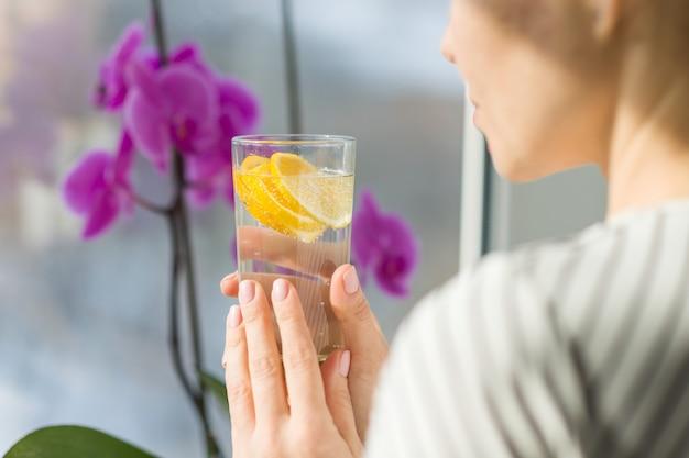 Trinkwasser der frau mit frischer organischer zitrone. Premium Fotos