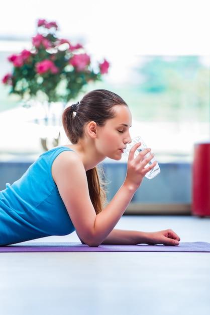 Trinkwasser der jungen frau im turnhallengesundheitskonzept Premium Fotos