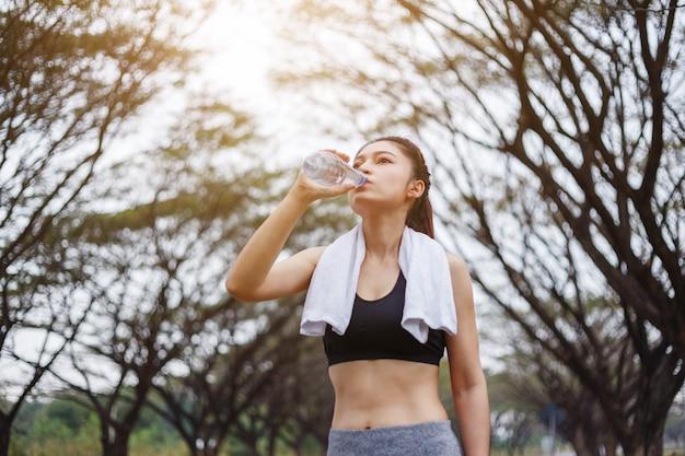 Trinkwasser der jungen sportlichen frau im park Premium Fotos