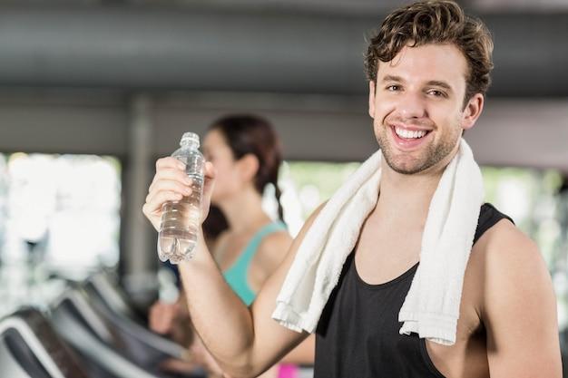 Trinkwasser des athletischen mannes beim laufen auf tretmühle in der turnhalle Premium Fotos