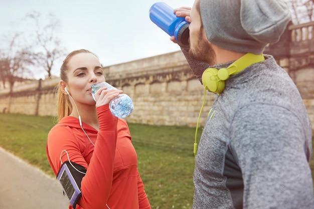Trinkwasser des glücklichen paares nach dem training Kostenlose Fotos