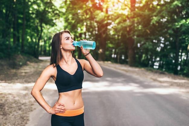 Trinkwasser des jungen eignungsmädchens im park Premium Fotos