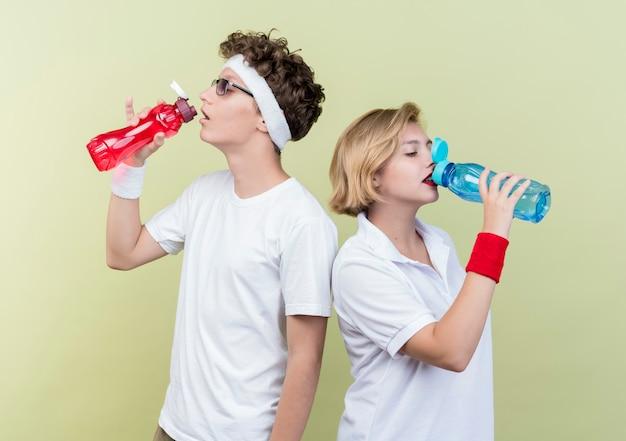 Trinkwasser des jungen sportlichen paares mann und frau nach dem training, das über lichtwand steht Kostenlose Fotos