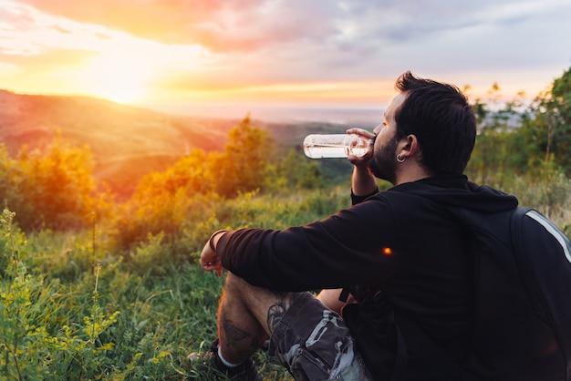 Trinkwasser des mannes und genießen des gebirgssonnenuntergangs Premium Fotos
