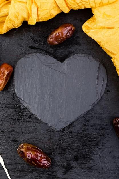 Trockene fruchtdaten in der goldenen schale nahe schwarzem herzen des schiefers. Premium Fotos