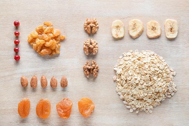 Trockene haferkörner mit früchten und nüssen auf holz Premium Fotos