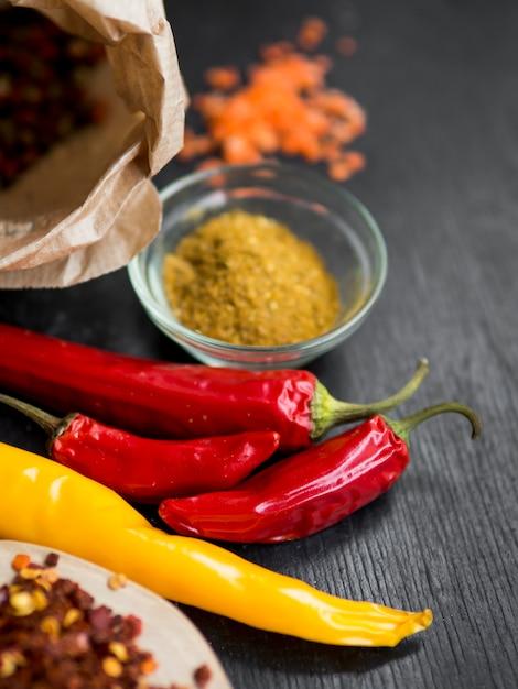 Trockene paprikas mit gewürzen auf schwarzem hintergrund Kostenlose Fotos